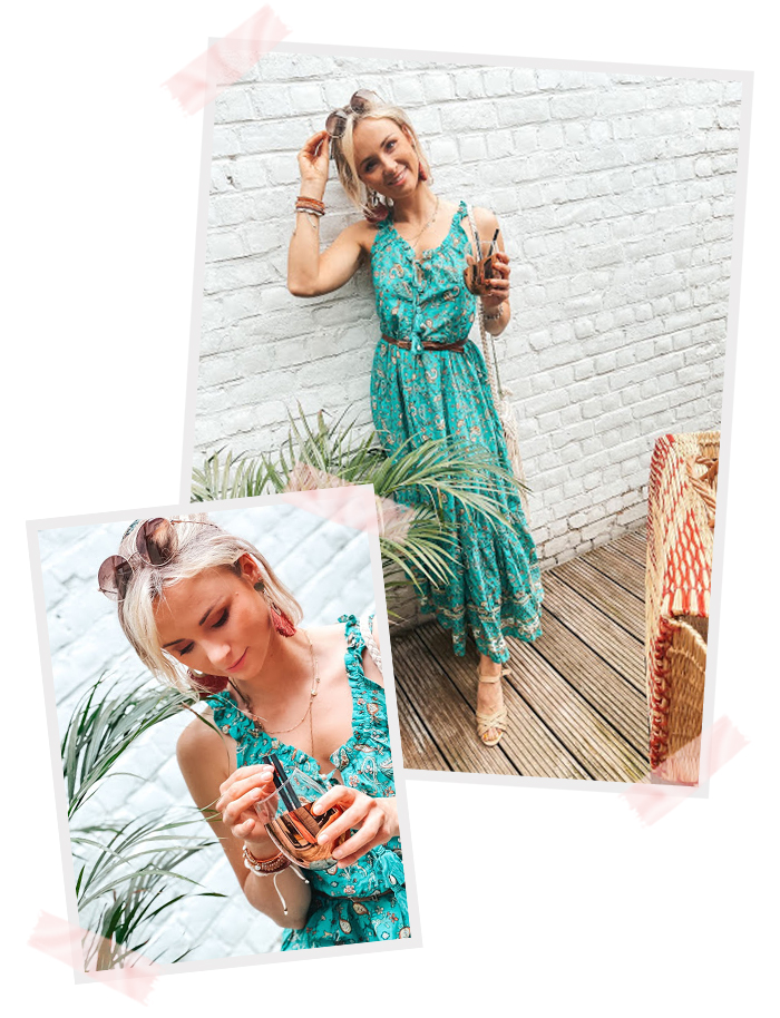 Nele wearing a green printed dress with a belt to accentuate her waist and heeled sandals. Standing next to a plant with a glass in her hand. Grabbing her sunglasses in her hair.