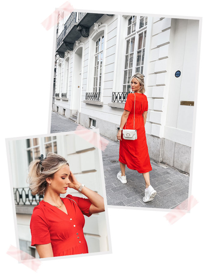 Nele wearing a red dress with sneakers and bag walking in the streets looking behind her.